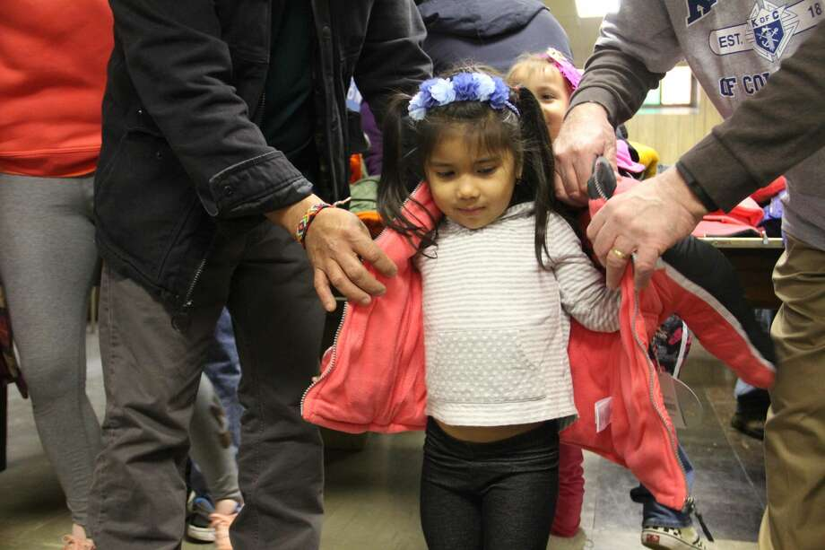 Children receive free coats from the Knights of Columbu Coats for Kids drive on Friday, Nov. 24, 2017 at St. John the Baptist Church in New Haven. Organizers said 300 coats were available for children.