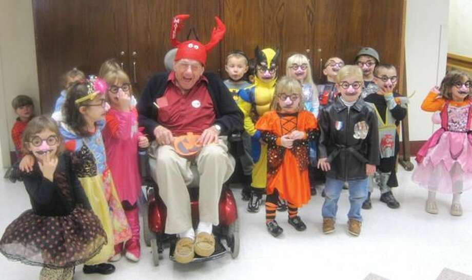 "Submitted Photo Masonicare Health Center resident ""grandpa"" Joseph Guarino and students from the Masonicare Child Development Center celebrate Halloween at the Center in Wallingford. Students from the pre-school class at the Masonic Child Development Center joined residents of Masonicare Health Center recently for a pizza party and celebration of one of their favorite holidays of the year - Halloween. Residents and staff were delighted to watch as the youngsters paraded in their colorful costumes - ""Groucho"" glasses and all - and distributed gifts of paper pumpkins hand made by the children."