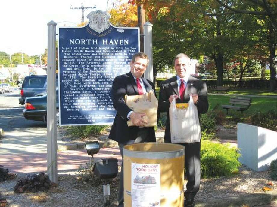 Photo courtesy of Valerie Goodkin Reverend Scott Morrow of the North Haven Congregational Church with First Selectman, Michael J. Freda commence the Holiday Food Drive with a receptacle at Town Hall.
