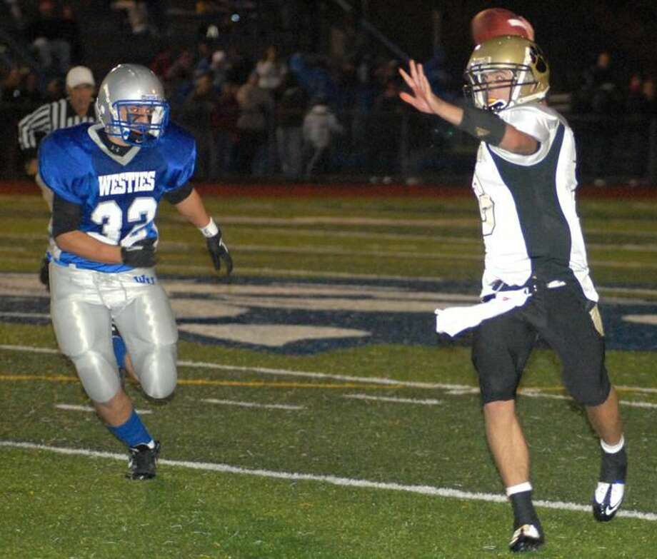 Photo by Dave Phillips Hand quarterback Zach Miller is chased by West Haven's Joe Hattani in the Tigers' 35-13 victory last Friday night at Ken Strong Stadium.