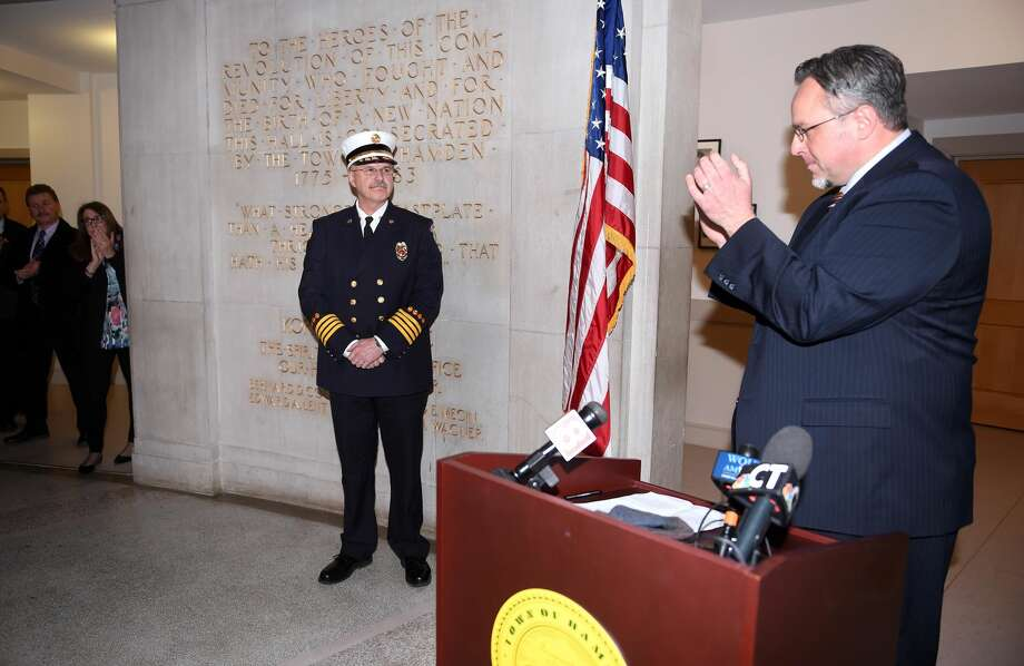 Hamden Mayor Curt Balzano Leng applauds Deputy Fire Chief Gary Merwede after announcing his appointment to Fire Chief at Hamden Memorial Town Hall on Dec. 20.