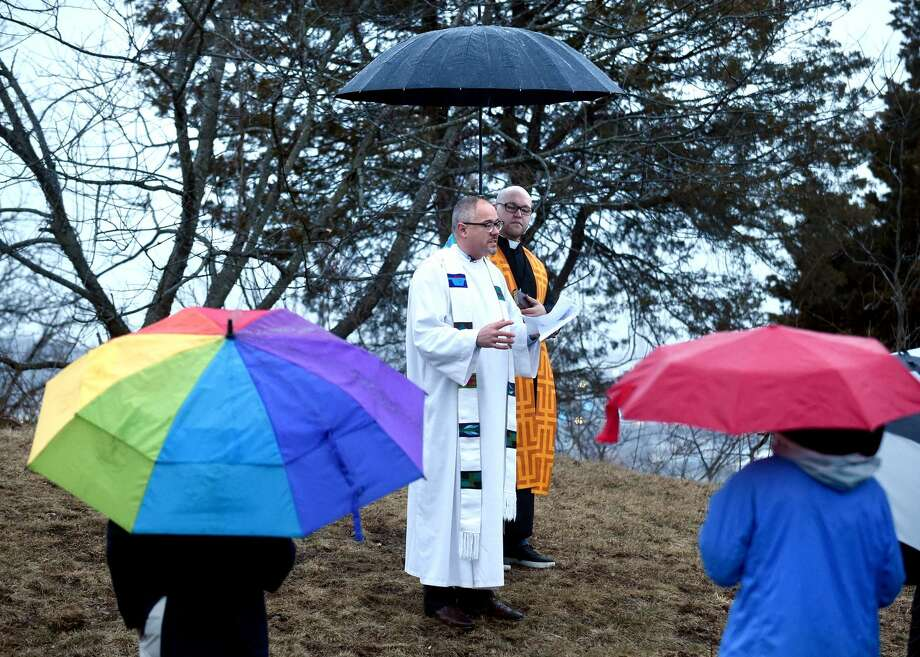 Rev. Edwin Perez, Jr., right, Minister for Social Justice at the United Church on the Green in New Haven, holds an umbrella for Rev. Paul Fleck, Pastor of Hamden Plains United Methodist Church in Hamden, during an Easter Sunrise Service at the summit of East Rock Park in New Haven on April 1, 2018.