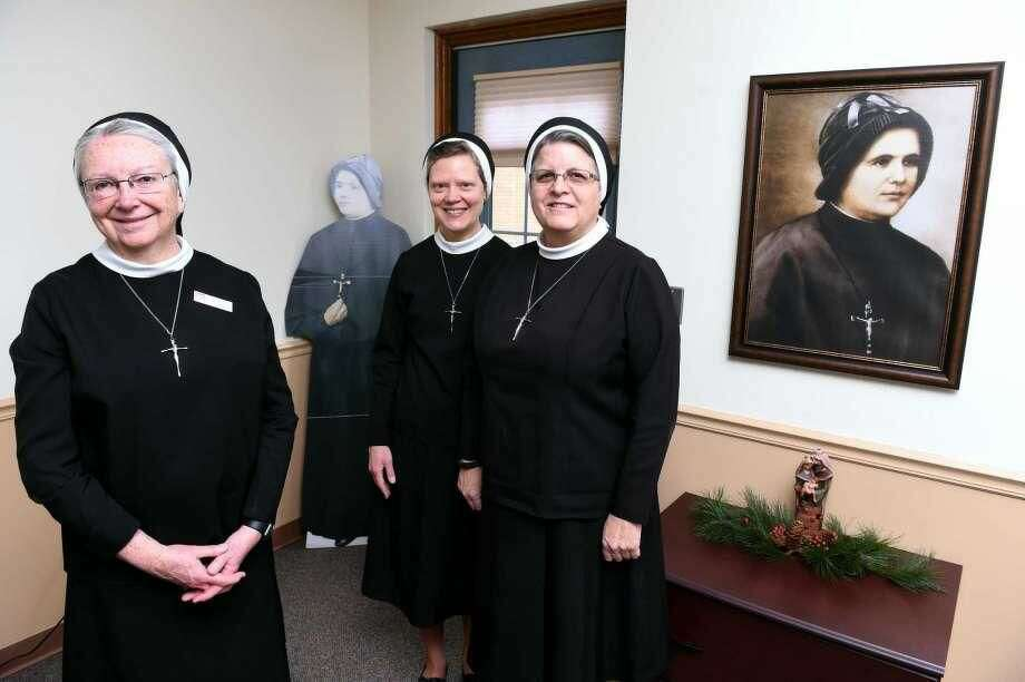From left, Sister Sheila O'Neill, president of Sacred Heart Academy, Sister Colleen Therese Smith, director of mission advancement for the Apostles of the Sacred Heart of Jesus, and Sister Mariette Moan, provincial councilor for the order, near photos of Mother Clelia Merloni at the Provincial House on Benham Street in Hamden on Dec. 17.