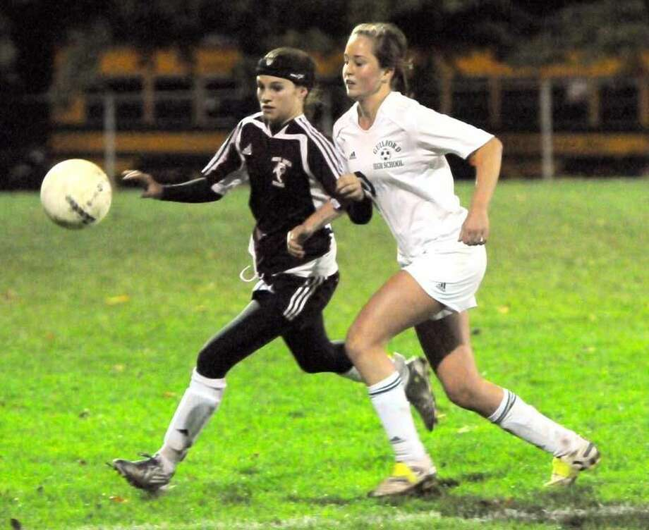 Photo by Peter Hvizdak/ Register Sarah Pandolfi and Guilford's Hannah Moore chase after the ball.