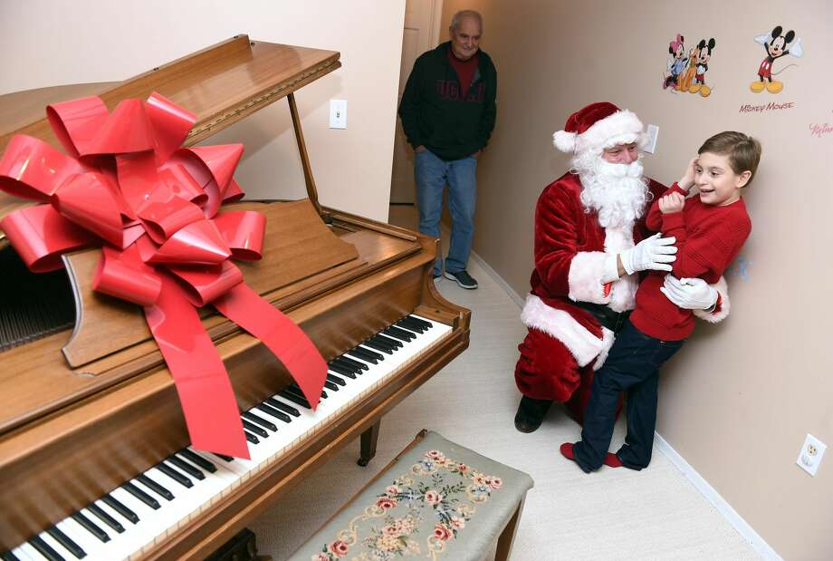 Alexander Stamboulidis, 9, thanks Santa Claus for the delivery of his Christmas wish, a baby grand piano, to his home in North Haven on Dec. 24, 2018. Michael Storz, president of the Chapel Haven Schleifer Center, filled in for Santa Claus.