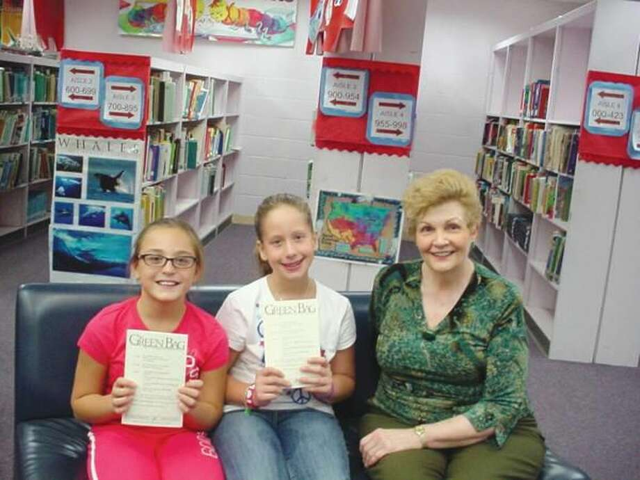 """Submitted Photo Ridge Road Elementary School students Chandler DeCusati and Alyssa Guarino are holding the journal called """"The Green Bag,"""" in which their letters appear. They are seated with Librarian Lydia Westerberg in the Ridge Road Library. """"The Green Bag"""" is a journal written for lawyers and read regularly by our Supreme Court Justices."""