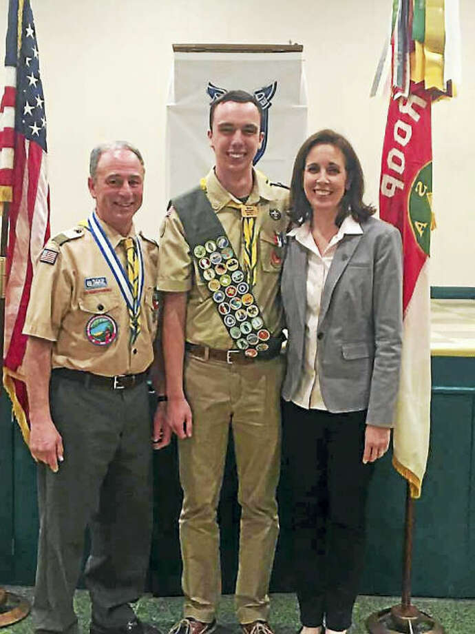 Contributed photo Scoutmaster Bill Earley congratulating Eagle Scout Jake Armstrong. At right is Brenda Armstrong, Jake's mother.