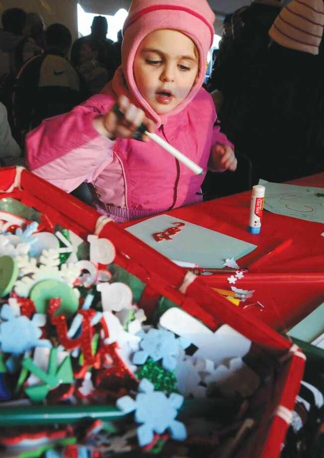 Photo by Brad Horrigan Carly Skorupski, 4, of Hamden, decorates her letter to Santa Saturday at the Hamden Silverbells Festival at Town Center Park.