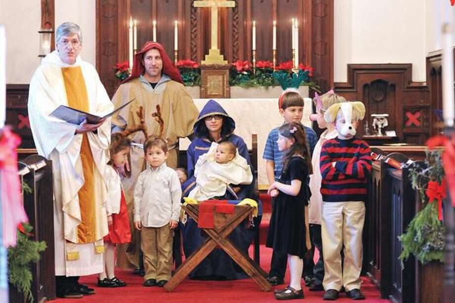 Photo by Peter Casolino Father Matt Lincoln, left, reads during the Children's Christmas pageant at St. John's Episcopal Church in North Haven on Christmas Eve.