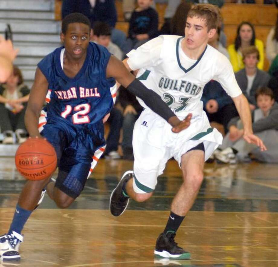 Photo by Dave Phillips Lyman Hall's Rich Bronson dribbles past Guilford's Jake Battipaglia in the Trojans' 97-61 victory last Friday night.