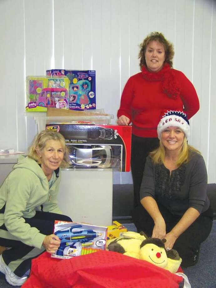 Submitted Photo Karen Sega from Holiday for Giving (left); Cindy Semrau, Vice President & COO for QChamber (right); and Liz Davis, Benefits Coordinator for QChamber (standing) show some of the toys donated at the chamber's Holiday Party to benefit Holiday for Giving in Wallingford.