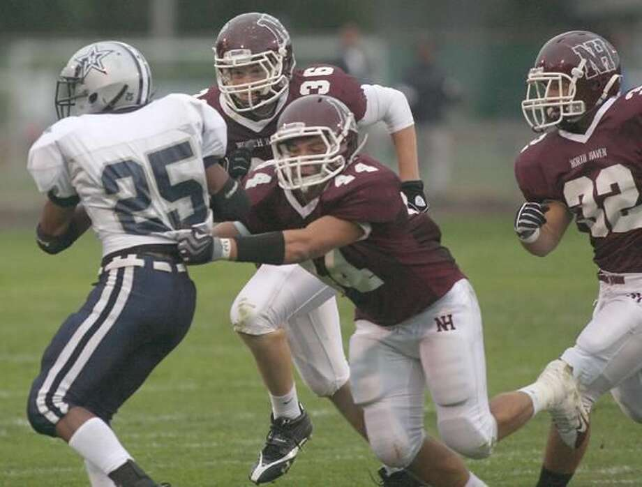 """Photo by Russ McCreven North Haven's Mark Zurlis tries to wrap up Hillhouse's Mario Callahan in the season opener. Coach Anthony Sagnella said Zurlis was the """"heart and soul"""" of the North Haven defense."""