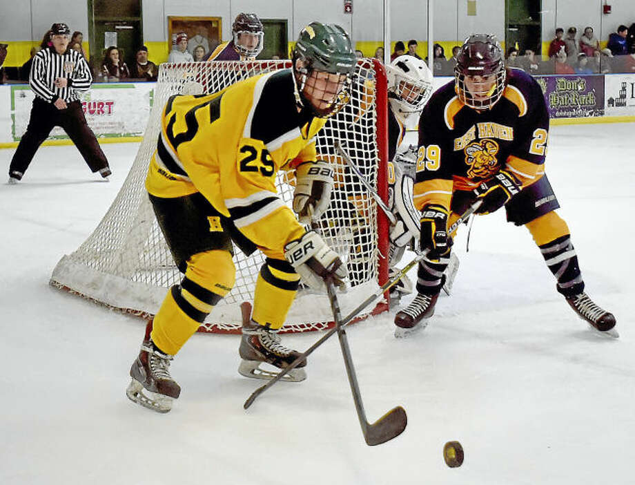 Hamden sophomore forward Raif Harris (25) battles East Haven senior Shawn Wagner Wednesday at Astorino Rink in Hamden. Harris led the Green Dragons with a hat trick in a 6-2 win over East Haven.