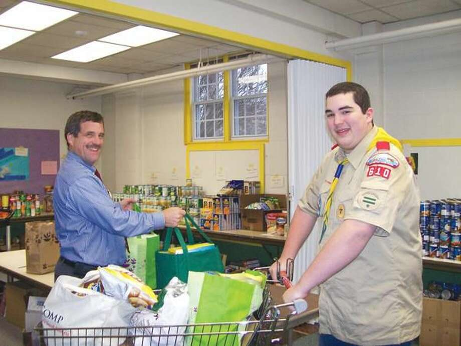 Photo by Lynn Fredricksen The Rev. Scott Morrow was thrilled to receive a food donation from Boy Scout Dean Richetelle of Troop 610 in Hamden. Richetelle collected non-perishable food and personal care items for the Food Bank's holiday distribution.
