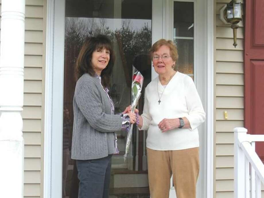 Submitted photo Jo Ann Begley, coordinator of the Caregiver Support Network at VNA Community Healthcare, gives Nancy Etter of North Haven a rose in honor of National Caregiver Month (November). Etter cares for her husband with Alzheimer's and attends the non-profit home care agency's monthly family caregiver support group meeting at their 2 Broadway location in North Haven.