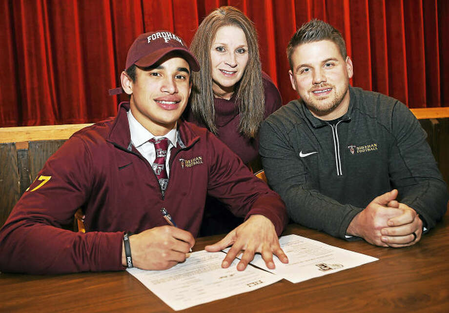 Sheehan senior running back Zach Davis signs a National Letter of Intent to play football at Fordham University Wednesday. Davis had 358.8 rushing yards per game, leading the nation, and led the state with 52 touchdowns and 3,588 rushing yards. Also pictured is Zach's mother, Tammy Davis and head coach John Ferrazzi.
