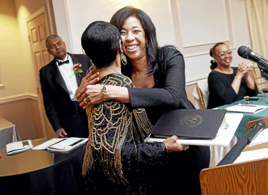 Carroll E. Brown (back to camera) hugs Rolan Joni Young Smith, Senior Partner at Berchem, Moses & Devlin, P.C., upon being awarded the Rev. Dr. E.R. Edmonds Humanitarian Award at the Carroll E. Brown Scholarships & Community Awards Dinner held at Fantasia in North Haven Feb. 25, 2017.