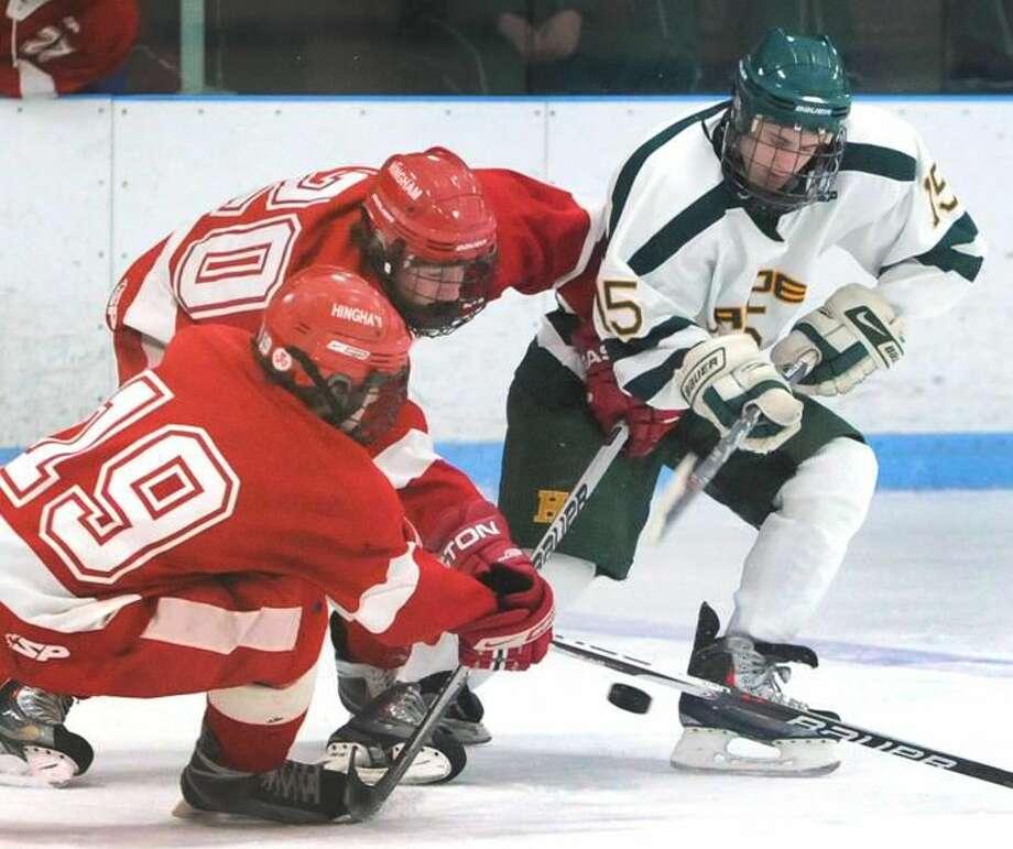 Photo by Peter Hvizdak/ Register Hamden's Zak Masotta battles Jake Magner, left, and Austin O'Connor, center, for the puck.