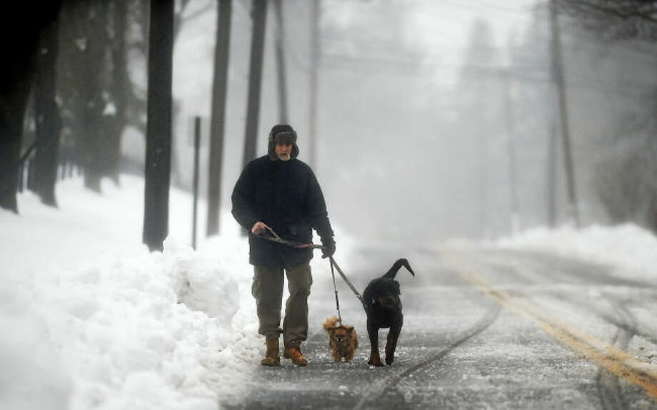 A Ridge Road resident takes his two dogs for a walk walk in Middletown during the blizzard,Tuesday, March 14, 2017. (Catherine Avalone/New Haven Register)