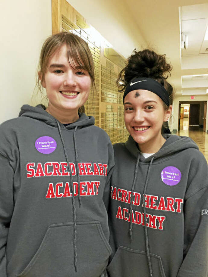 """Contributed photo Sacred Heart Academy Seniors Elizabeth Lamont of Hamden and Ashley Gerckens of Derby proudly wear """"I Phone Fast. Can u?"""" stickers on Ash Wednesday. This campaign invited students to silence their devices to help deepen their relationship with God as they prepare for Easter."""