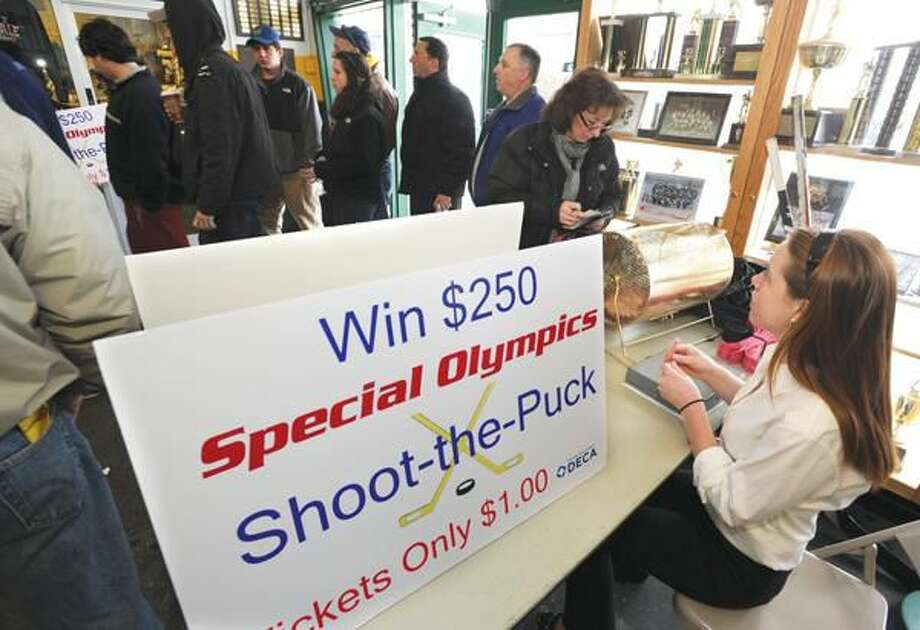 Photo by Mara Lavitt Hamden High School DECA member Rachel Dowe developed a Shoot the Puck project benefitting CT Special Olympics. Here she takes in raffle tickets at the door for the game between Fairfield Prep and Hamden High School Saturday at the Astorino Rink.