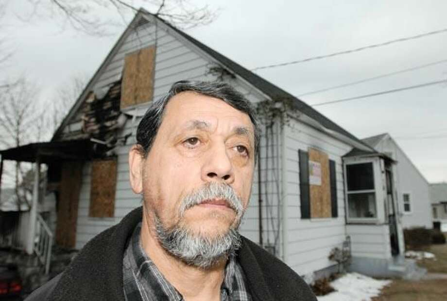 Photo by Peter Hvizdak Ivan Cordero of Hamden, 59, rescued a woman from her burning home after he saw black smoke billowing from the 398 Pine Orchard Road single family residence in Hamden Jan. 6. In the photo Cordero is standing on a sidewalk by the house. January 7, 2011 ph2233 #1736 Connecticut