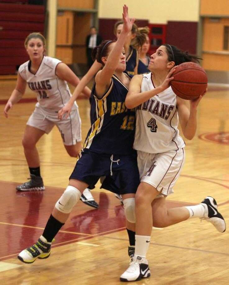 Photo by Russ McCreven North Haven's Olivia DiCapua looks to shoot while East Haven's Julie Waters defends in the Indians' 39-28 victory.