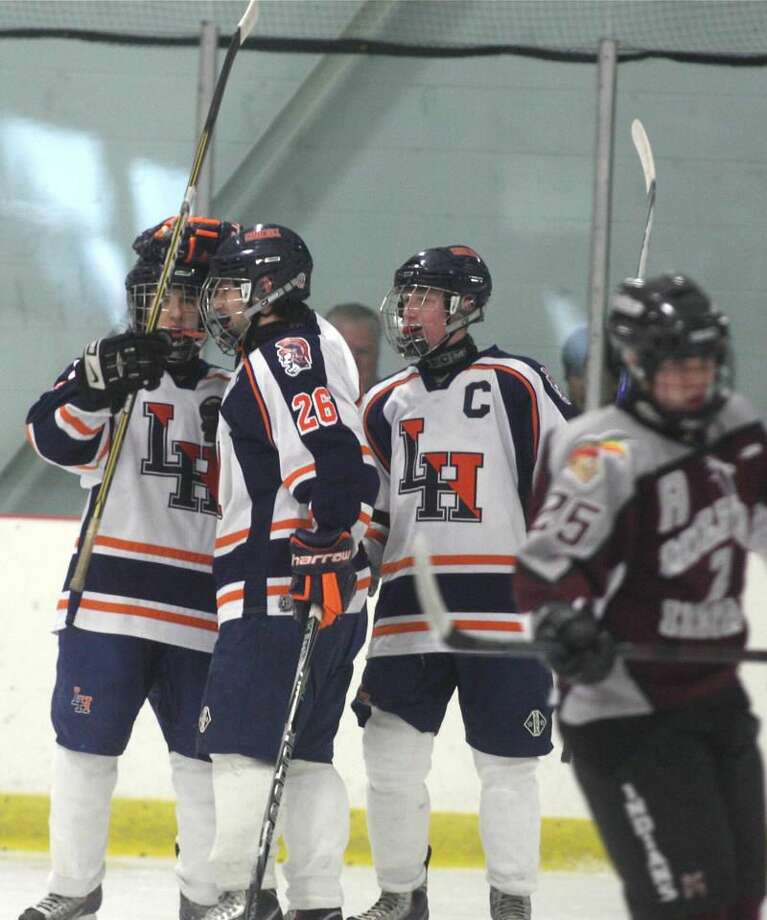 Photo by Russ McCreven Lyman Hall's Adam McKay (26) celebrates a goal with teammates in the Trojans' 6-0 victory over Milford Friday afternoon at the Northford Ice Pavilion.