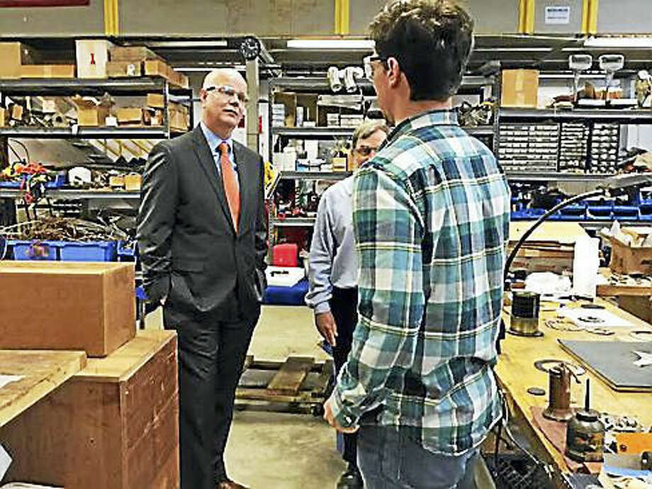 Kevin Lembo at Precision Combustion Thursday talks to workers.