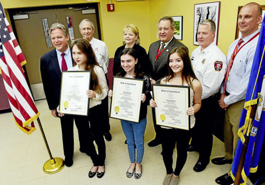 """From left, Branford High School essay runner-up Viktoria Sinani, winner Kelly Tiernan and runner-up Samantha Esposito receive recognition for their submissions to rename """"Negro Heads"""" rocks off Branford's shoreline. Also pictured are, from left, state Sen. Ted Kennedy Jr.; Dr. Roger Lowlicht of Branford; Community Foundation board member Stephanie Donegan Dietz; Branford Superintendent of Schools Hamlet Hernandez; Branford Fire Chief Tom Mahoney; and Branford High School Principal Lee Panagoulias."""