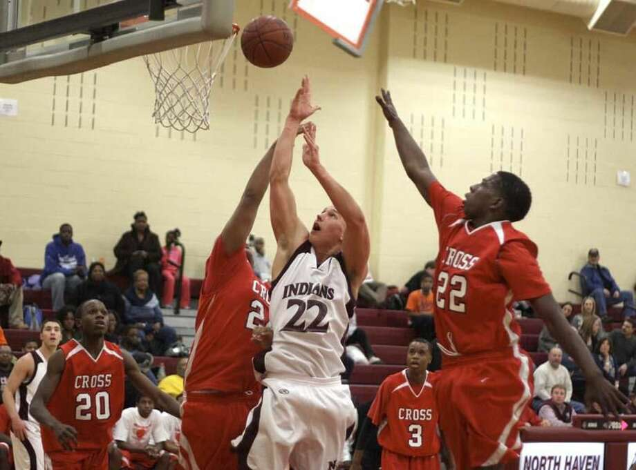 Photo by Russ McCreven North Haven's Steve McCarthy shoots over Cross' Gerald McClease in the Indians' 71-52 loss Monday night.