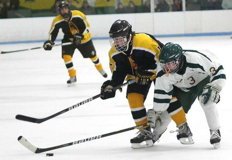 Photo by Russ McCreven Hamden's Patrick Lynch tries to gain control of the puck against Amity.