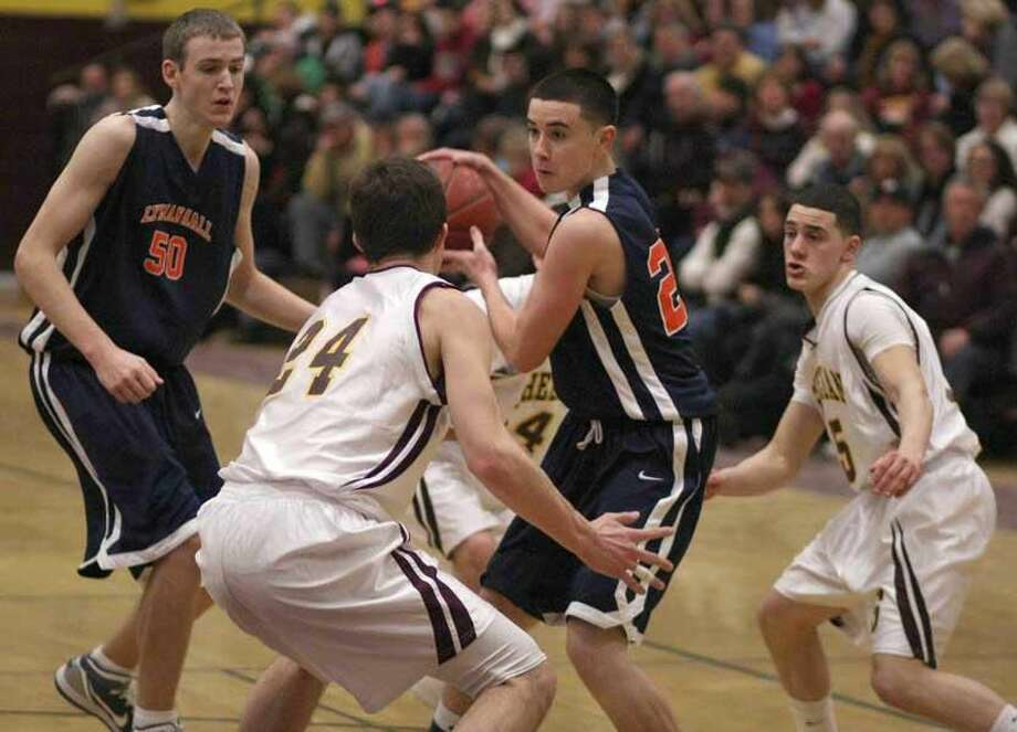 Photo by Russ McCreven Lyman Hall's Kevin Ruys looks to pass while being surrounded by Sheehan players in the Trojans' 61-50 victory Monday night at Sheehan.