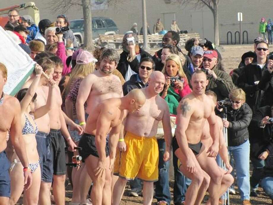 Photos courtesy of David Marchesseault, Rotary Secretary Dr. Richard Bassett (yellow swimsuit) takes the plunge at Lighthouse Point for his personal goal to raise funds in the fight against breast cancer.