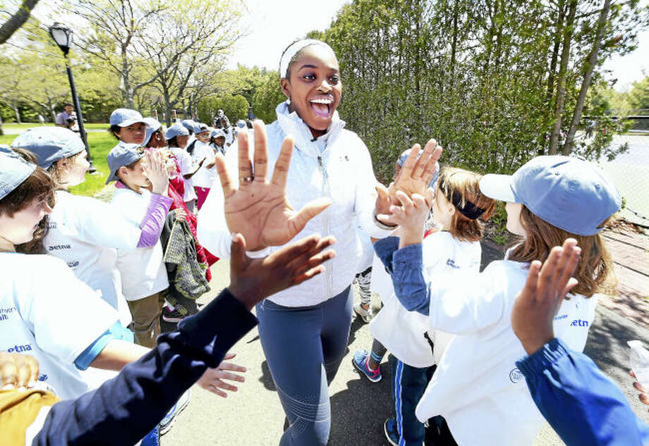 Professional tennis player Sloane Stephens (center) share high-fives with third graders from New Haven Public Schools during a free tennis clinic at the Connecticut Tennis Center courts in New Haven Tuesday.