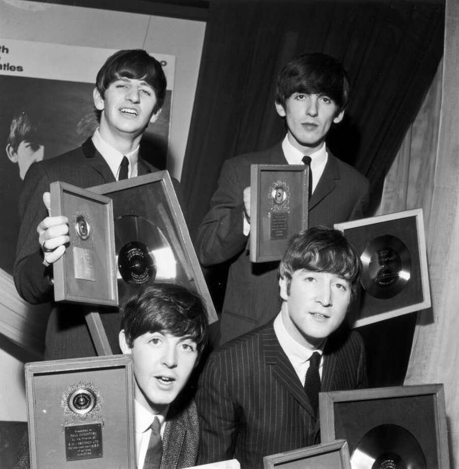"""The Beatles holding their silver LP and EP discs presented to them by EMI records in London to mark sales of records including the LP """"Please Please Me"""" and """"Twist And Shout,"""" the best-selling EP of all time. Clockwise from back left: Ringo Starr, George Harrison, John Lennon and Paul McCartney."""