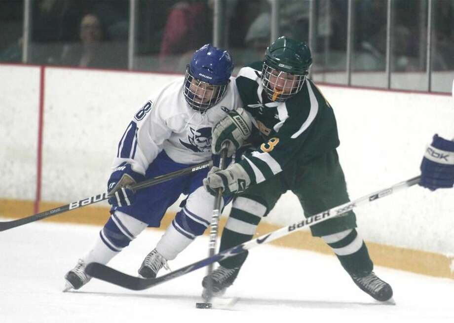 Photo by Russ McCreven Hamden's Pat Lynch battles West Haven's Austin Hansen for control of the puck in the Dragons' 7-0 victory.