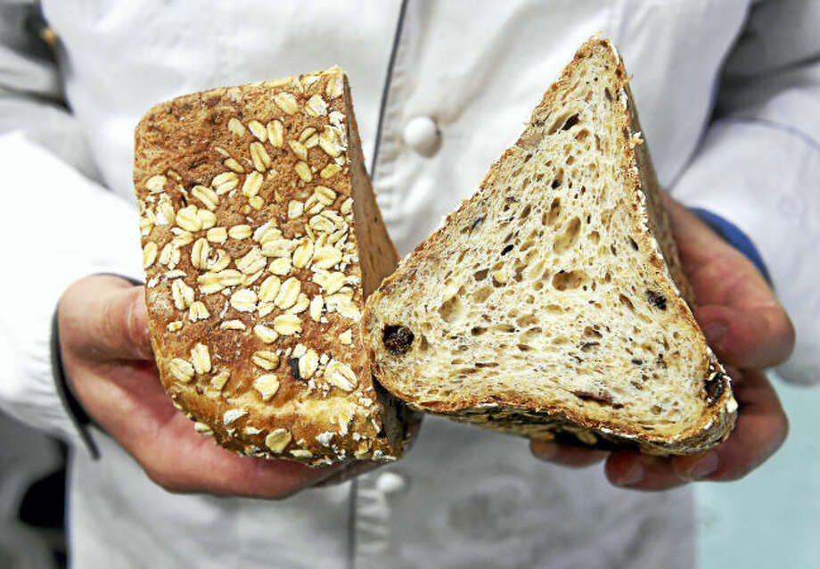Andrea Corazzini, owner and general manager of Whole G Bakery, holds a cross section of the MuesliBrot.