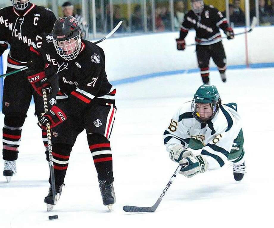 Photo by Peter Casolino/ Register Hamden's C.J. Carignan dives for the defensive block as New Canaan's Philip Prins drives toward the goal in the Green Dragons' 2-0 loss.
