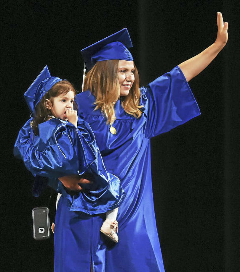 Carla Miranda Ramones and her 3-year-old daughter Sophia on stage to receive her associate degree in liberal arts and science at Gateway Community College commencement Thursday at the Oakdale Theatre in Wallingford.