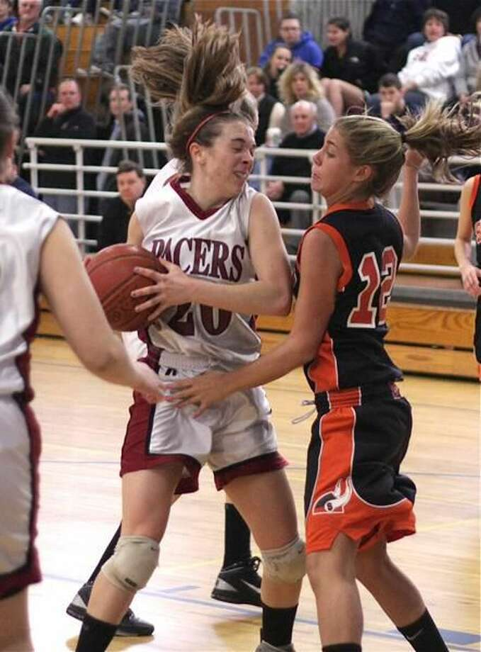 Photo by Russ McCreven Sacred Heart Academy's Natalie Bastian tries to maker her way past Shelton's Lauren McCone in the SCC quarterfinals Saturday at West Haven. Shelton won 59-57.