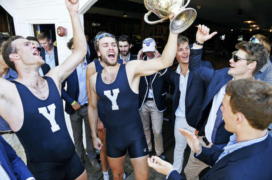 Yale bowman Ollie Wynne-Griffith hoists the Sexton Cup as the Bulldogs celebrate the heavyweight crew team's win at the annual Harvard/Yale regatta in Ledyard.
