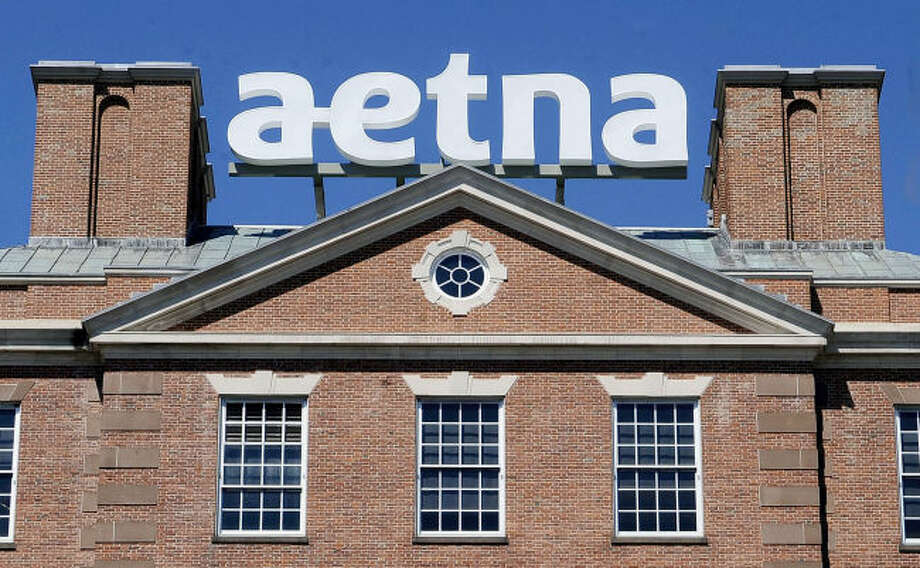 In this Tuesday, Aug. 19, 2014, file photo, a sign for Aetna Inc., sits atop a building at the company headquarters in in Hartford, Conn. Health insurer Aetna Inc. has made a deal to buy competitor Humana Inc. in a $37 billion deal the companies say would create the second-largest managed care company, it was announced Friday, July 3, 2014.