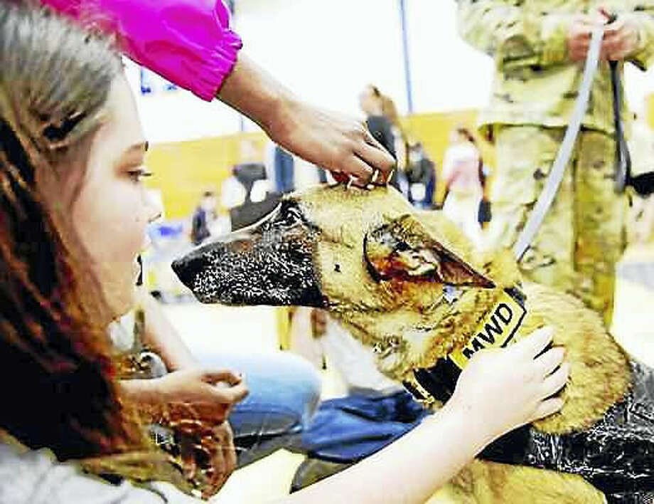Peter Hvizdak — New Haven Register. Melissa Pope of Hamden, 13, left, pets U.S. Army Military Working Dog Balou, a Belgian Malinois handled by Army Sgt. Christopher Rufini during the town's Veterans Awareness Day, sponsored by the Hamden Veterans Commission Wednesday at Quinnipiac University.