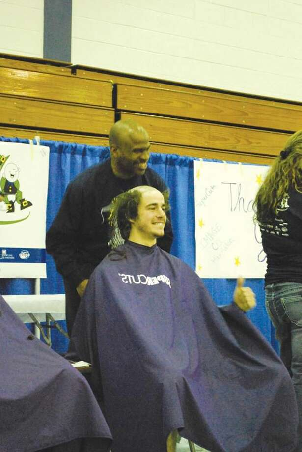 Submitted Photo De'Sean D. Rouse, standing, manager of Supercuts of Hamden, shaves the head of Quinnipiac University student Marc Villalongue at the St. Baldrick's event.