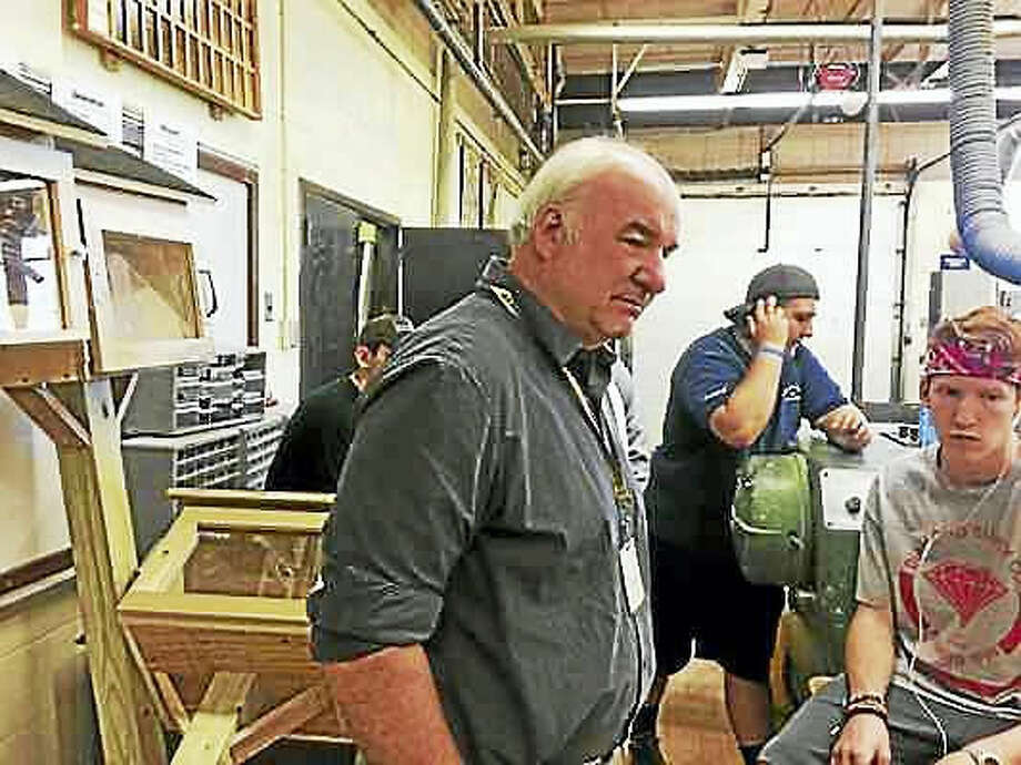 LUTHER TURMELLE — NEW HAVEN REGISTER Technology education teacher Alan Oblon, who is retiring after 38 years, meets with some of the students who helped build the book exchange boxes.