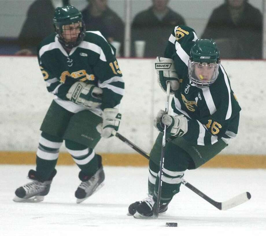 Photo by Russ McCreven Hamden assistant captain C.J. Carignan controls the puck as teammate Sean O'Keefe looks on.