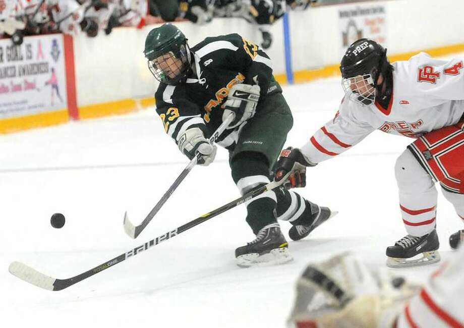 Photo by Brad Horrigan/Register Hamden's Tim Lee gets a shot off past Fairfield Prep defenseman Sean Henry during the Dragons' 5-2 loss in the Division I quartefinals.