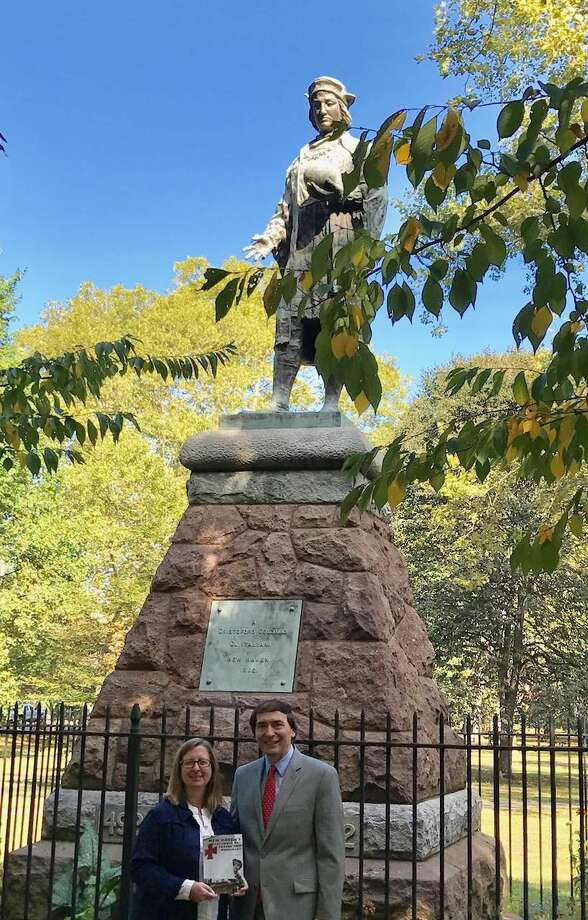 By the Columbus monument, the author of the book Laura A. Mancaluso PhD presents a copy of the book to Alfonso Panico, Former Vice Consul of the Republic of Italy and Former President of the Columbus Day Committee Inc. of New Haven.