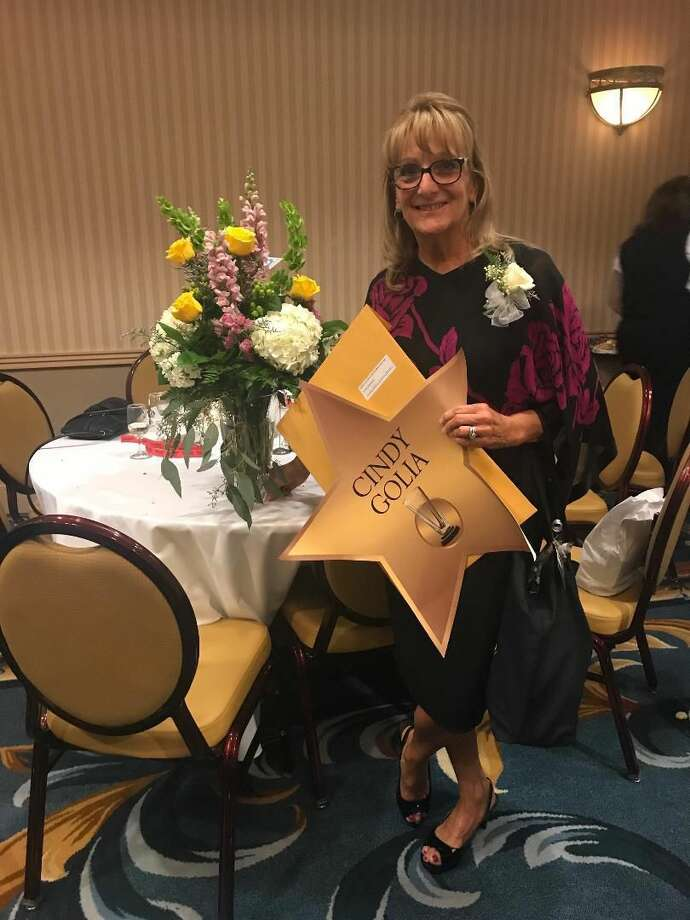 Cindy Golia holding gold star and citation.